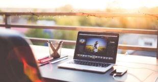 Zit buiten in de zon achter je laptop een online cursus te volgen