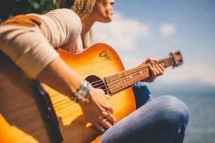Vrouw die gitaar aan het spelen is