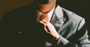Man in strak pak die zijn hand op zijn das heeft, hij is klaar voor een nieuwe uitdaging in zijn carriere
